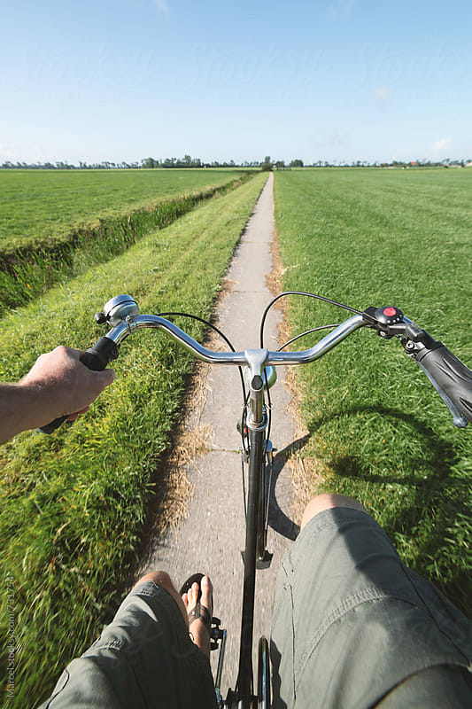Man in shorts cycling on rural path by Marcel for Stocksy United