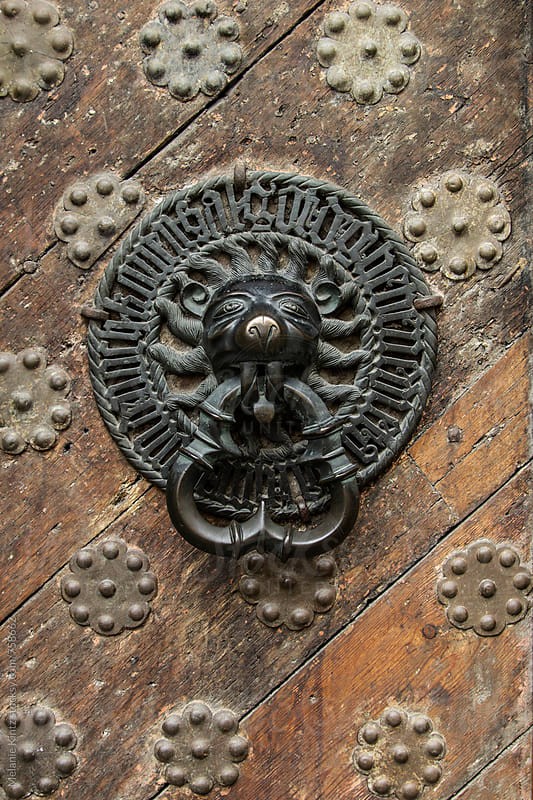 Lionhead door handle on an old door by Melanie Kintz for Stocksy United
