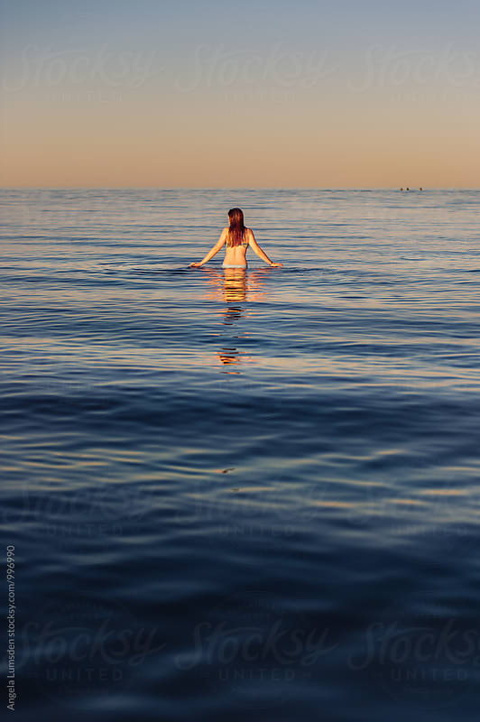 Girl walking in water at sunset by Angela Lumsden for Stocksy United