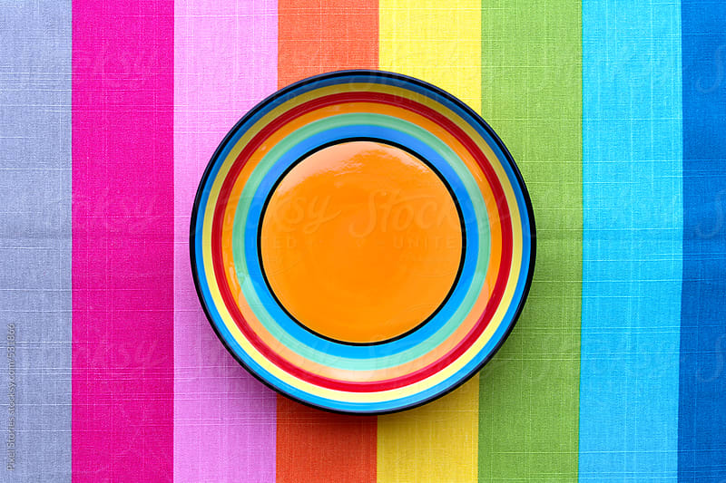 Colorful plates on colorful cloth by Pixel Stories for Stocksy United
