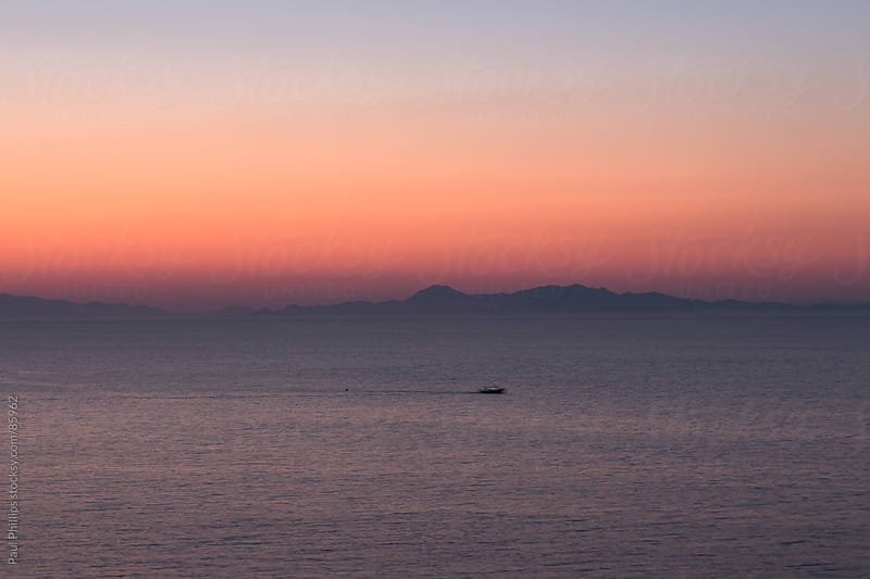 Just after sunset view across the sea looking towards Turkey by Paul Phillips for Stocksy United