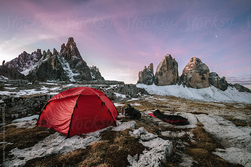 red tent in front of the famous three pinnacles at sunrise by Leander Nardin for Stocksy United