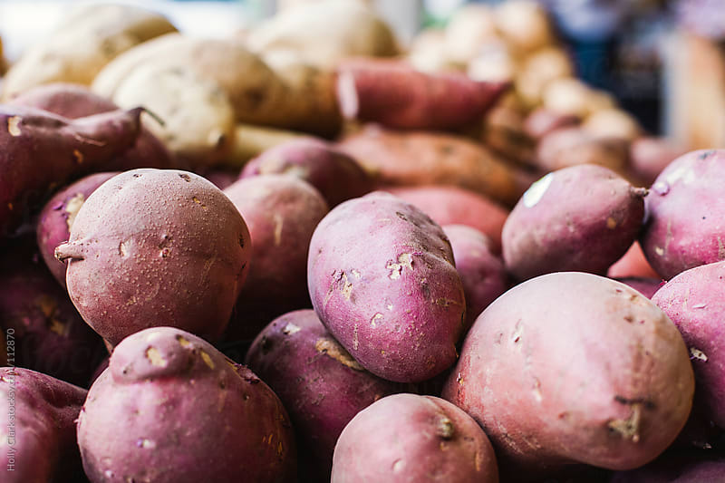Potatoes and yams for sale at an outdoor market. by Holly Clark for Stocksy United