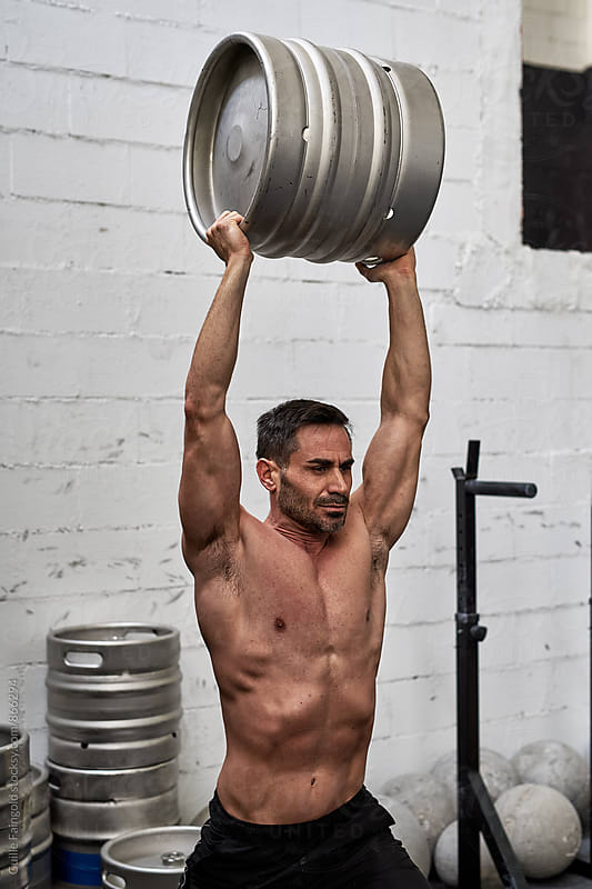 Man carrying a draft in a gym by Guille Faingold for Stocksy United
