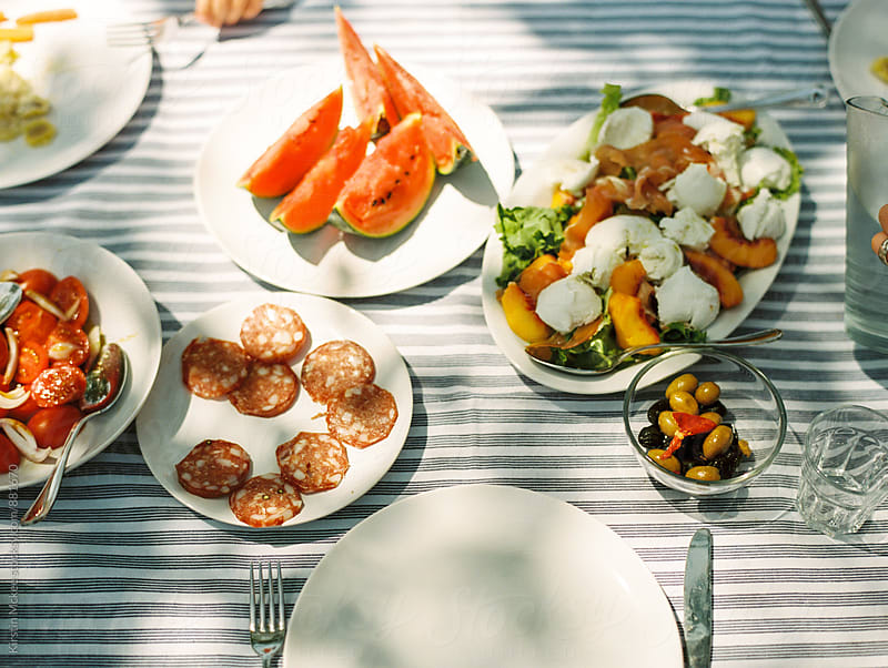 Lunch on a table under the shade, in Italy by Kirstin Mckee for Stocksy United