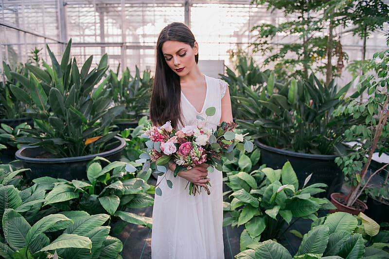 Young woman surrounded by plants holding flowers bouquet by Adrian Cotiga for Stocksy United