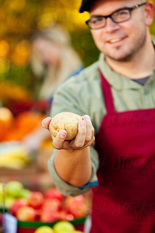 Farmer's Market: Focus on Potato in Hand by Sean Locke for Stocksy United