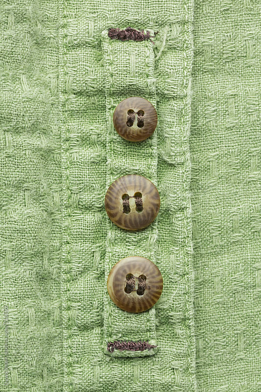 Three replacement buttons sewn on the inside of a shirt bracket. by David Smart for Stocksy United