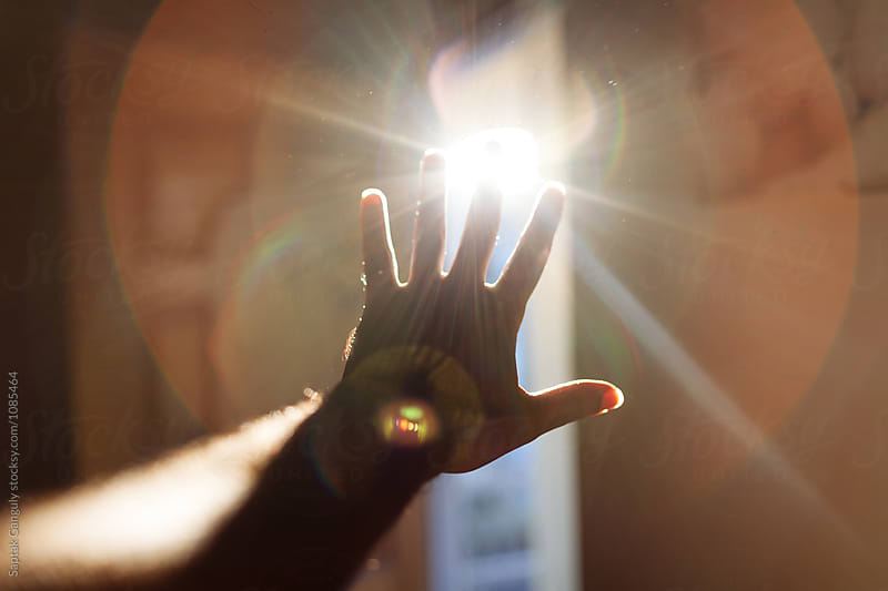Hand reaching out to sunrays by Saptak Ganguly for Stocksy United