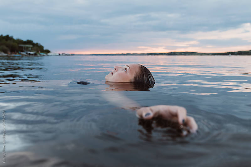 Beautiful woman floating in calm water at sunset by Carey Shaw for Stocksy United