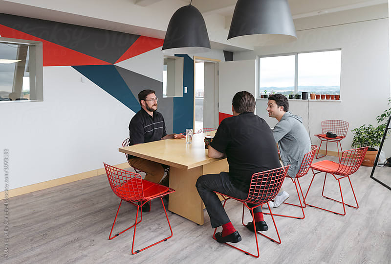 Three men meeting at kitchen table in office environment by Rob and Julia Campbell for Stocksy United