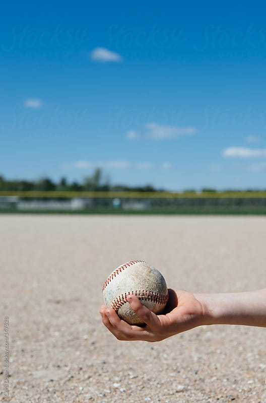 Child's arm with baseball on athletic field by Cara Dolan for Stocksy United