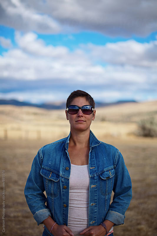 Strong woman in the desert wearing jean jacket and sunglasses on a cloudy day by Carleton Photography for Stocksy United