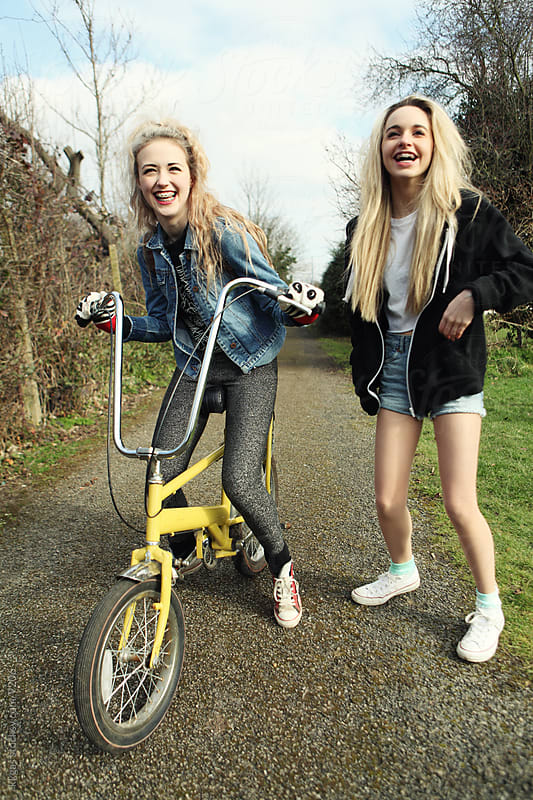 Pretty teenagers walking and cycling together. by kkgas for Stocksy United