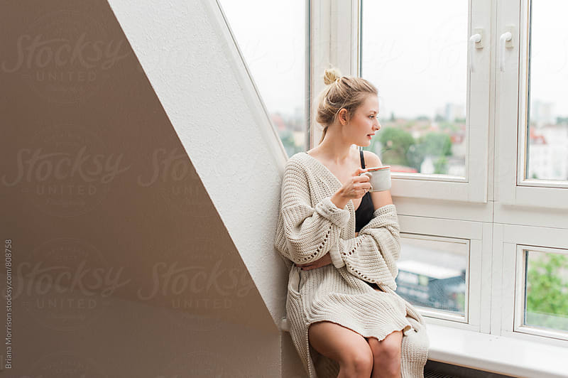 Young Woman in Her Pajamas Sitting in a Window Drinking out of a Mug by Briana Morrison for Stocksy United
