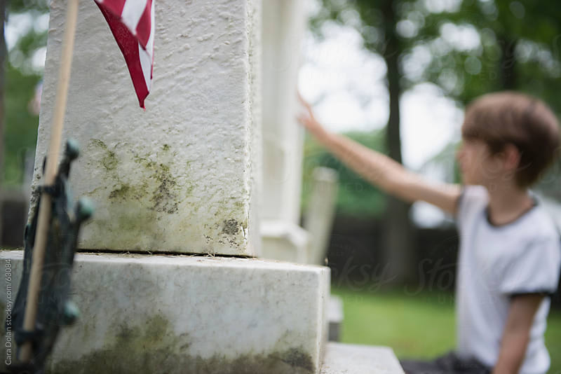 Child places his hand on a gravestone in a cemetery  by Cara Dolan for Stocksy United