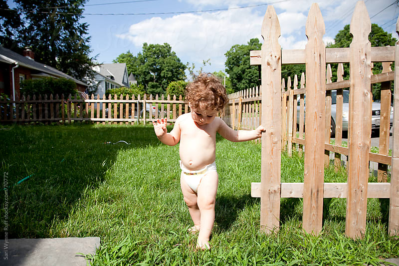 Dark Curly Haired Toddler with Picket Fence by Sari Wynne Ruff for Stocksy United