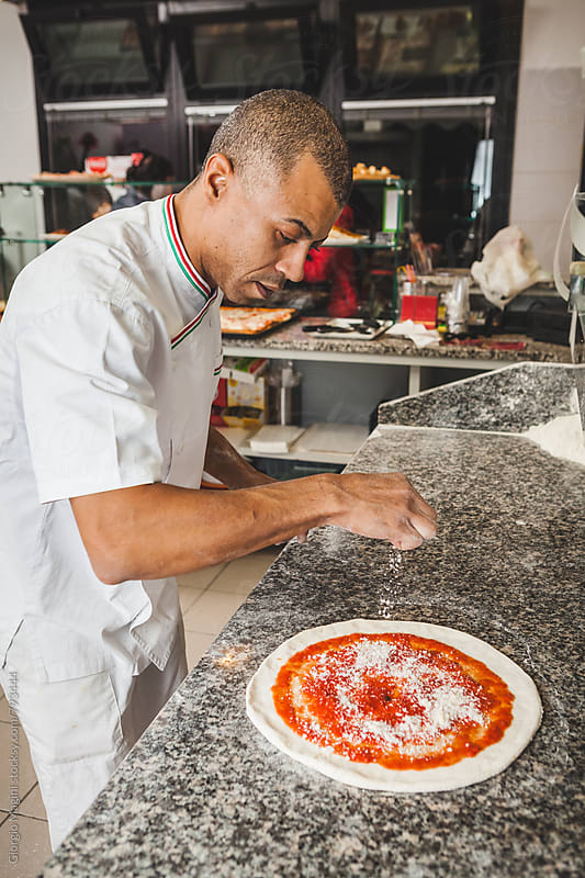 Pouring Parmesan Cheese on the Raw Dough of a Pizza by Giorgio Magini for Stocksy United