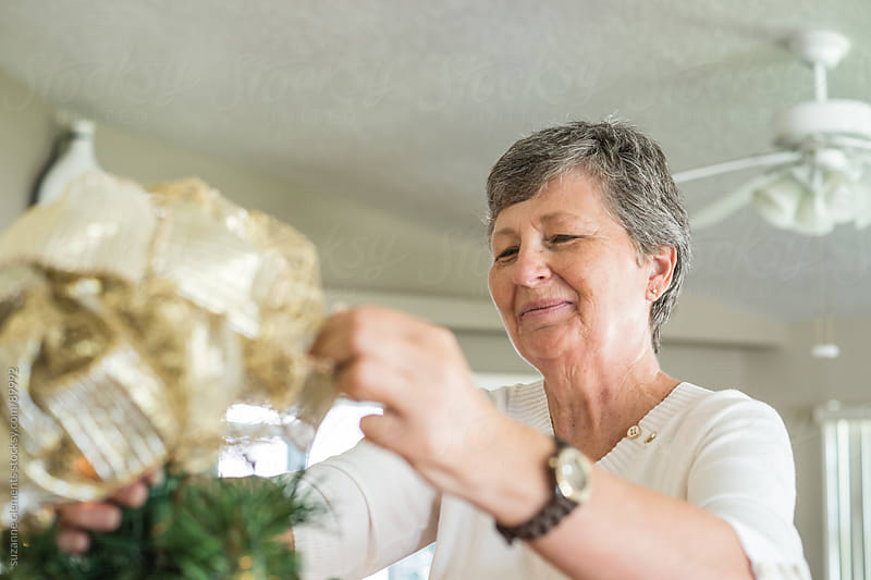 Woman Cheerfully Decorates her Christmas Tree by suzanne clements for Stocksy United