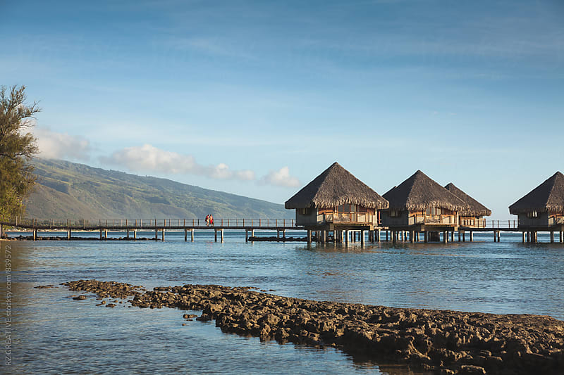 Over water bungalows in the shallow water of the lagoon in Tahiti. by RZ CREATIVE for Stocksy United