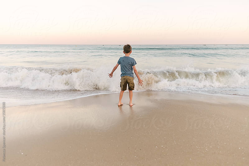 Boy faces the waves of the sea as they come towards him by Rebecca Spencer for Stocksy United