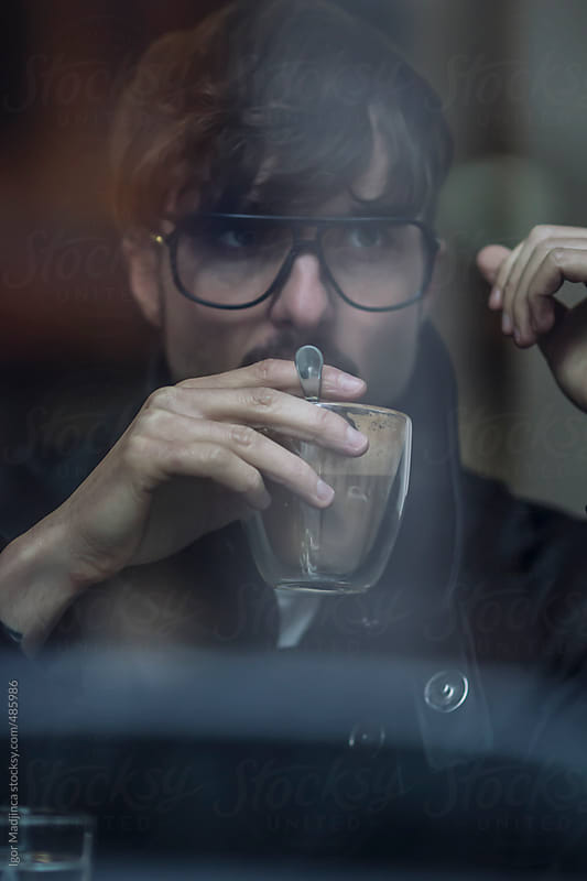 man with glasses drinking coffee in the  restaurant window, a street reflection  by Igor Madjinca for Stocksy United