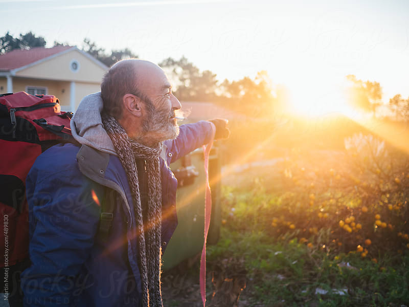 Homeless man pointing his hand into the sunrise by Martin Matej for Stocksy United