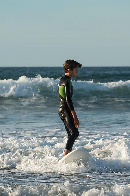 Boy learning how to surf by Marta Muñoz-Calero Calderon for Stocksy United