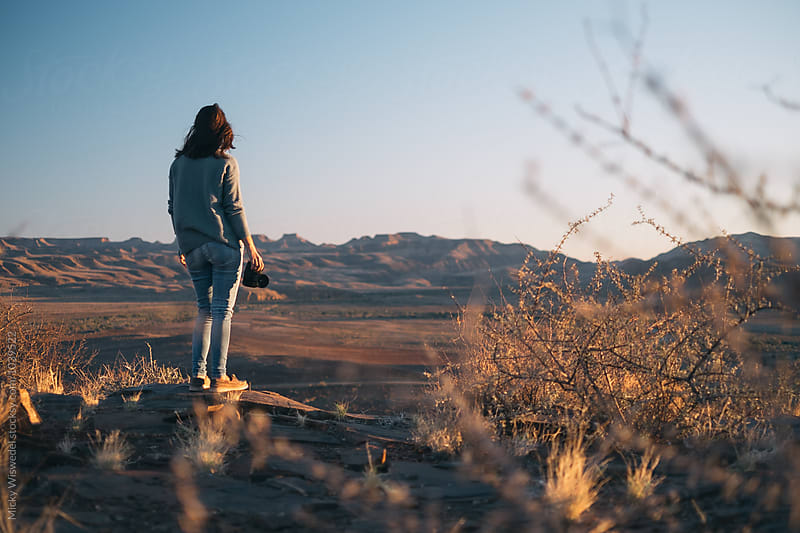Woman and holding camera and enjoying an expansive desert view by Micky Wiswedel for Stocksy United