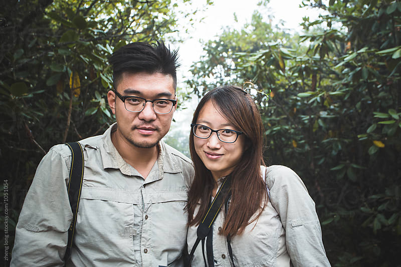 Young couple standing on the wooden by zheng long for Stocksy United