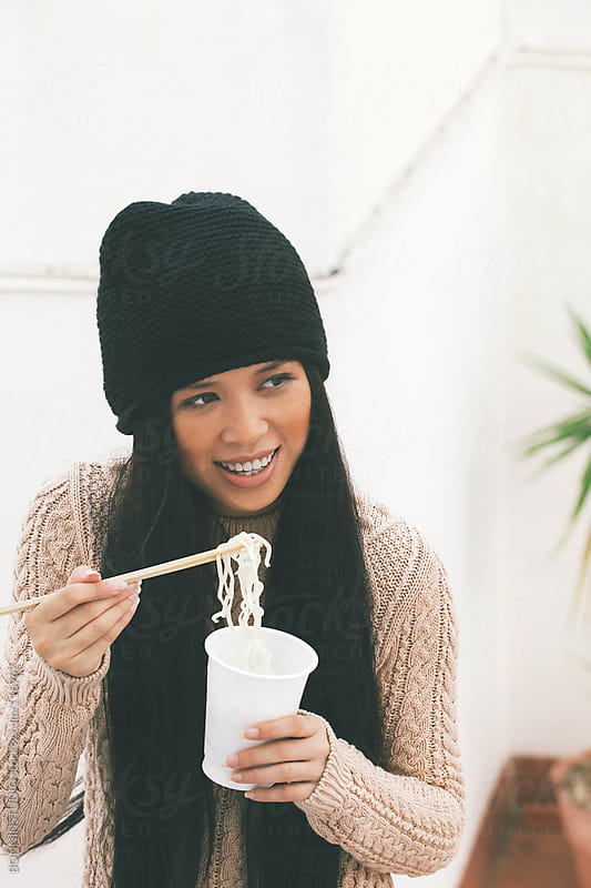 Young chinese woman eating noodles in outdoors. by BONNINSTUDIO for Stocksy United