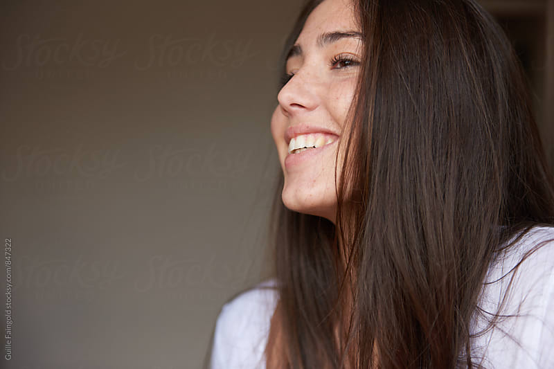 Close-up of attractive young woman smiling  by Guille Faingold for Stocksy United