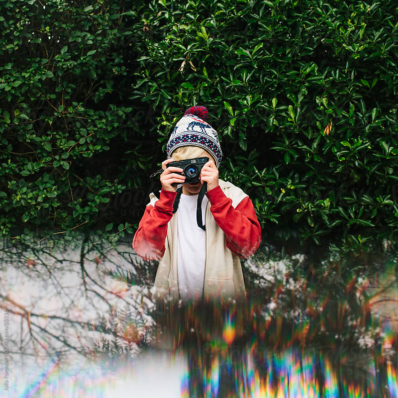 Bright playful image of a cool tween boy using a film camera. by Julia Forsman for Stocksy United