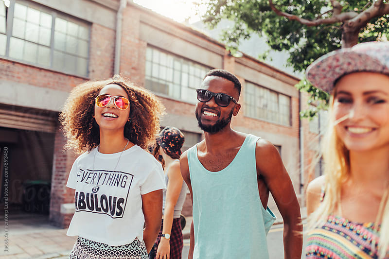 Smiling young couple walking with friends on street  by Jacob Lund for Stocksy United