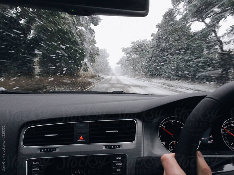 View from inside a car driving in the snow.  by Liam Grant for Stocksy United