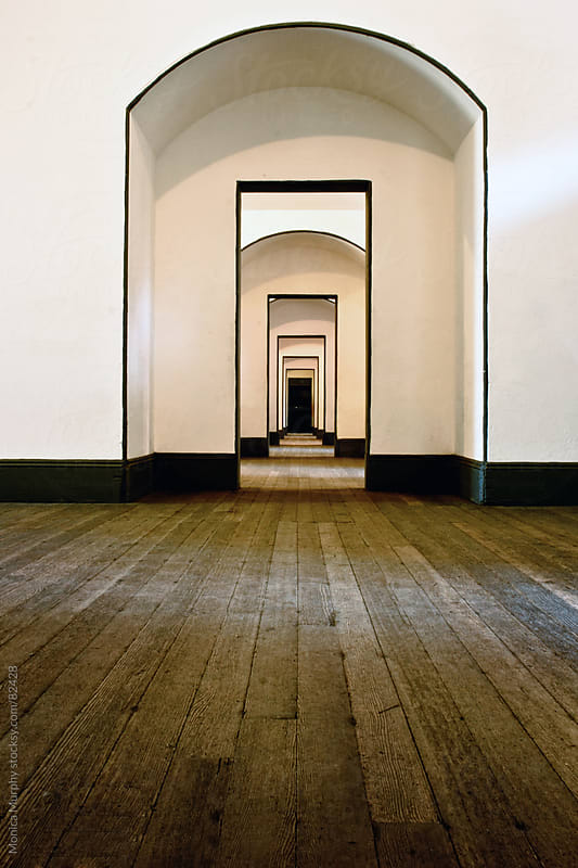Perspective of long hallway with multiple doorways by Monica Murphy for Stocksy United