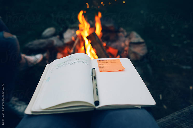 Campfire stories. Drawing and taking notes next to a campfire during travels by Denni Van Huis for Stocksy United