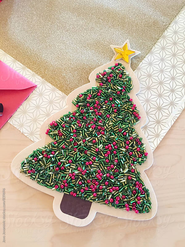 Christmas tree paper ornament sitting on table covered with wrapping paper by Jovo Jovanovic for Stocksy United