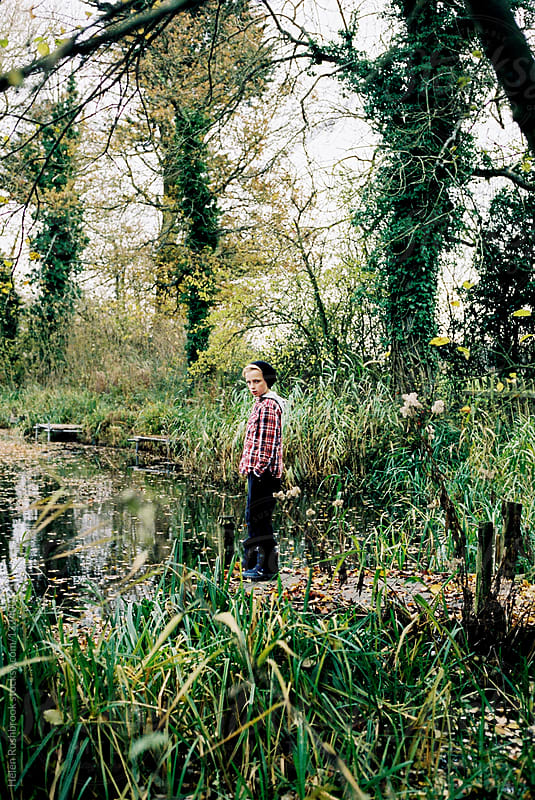 Boy by a lake by Helen Rushbrook for Stocksy United