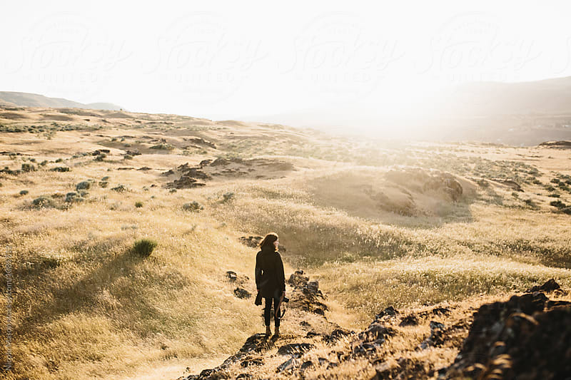 woman exploring mountainous desert landscape at sunset by Nicole Mason for Stocksy United