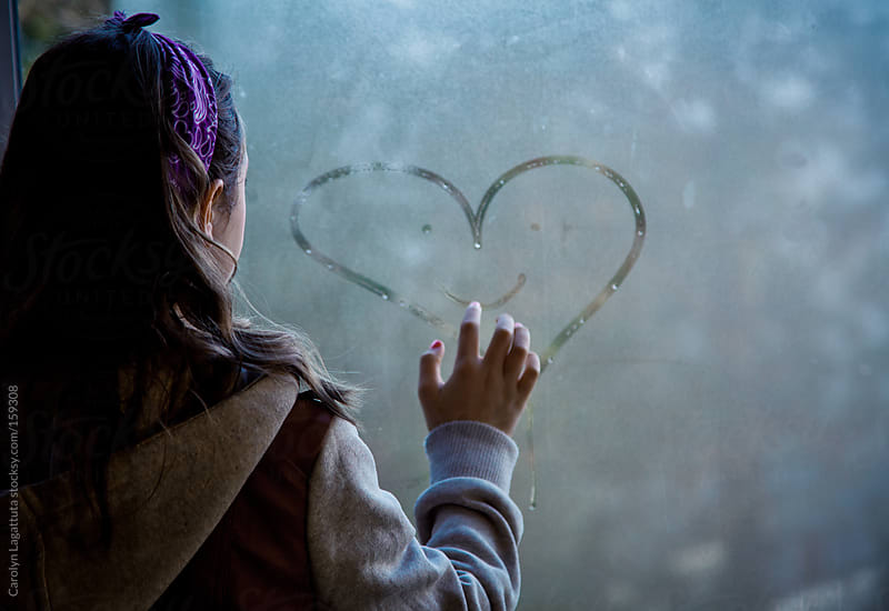 Young girl drawing a smiling heart on a window by Carolyn Lagattuta for Stocksy United
