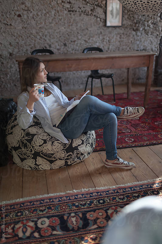 Young Woman Reading a Book at Home by HEX. for Stocksy United