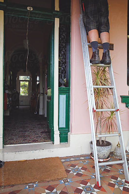 Anonymous man's legs up a ladder in front of his house doing maintenance by Natalie JEFFCOTT for Stocksy United