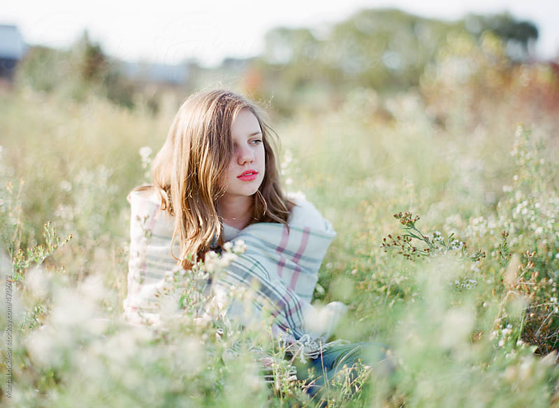 Teen girl sitting in a field wrapped in a flannel blanket by Marta Locklear for Stocksy United