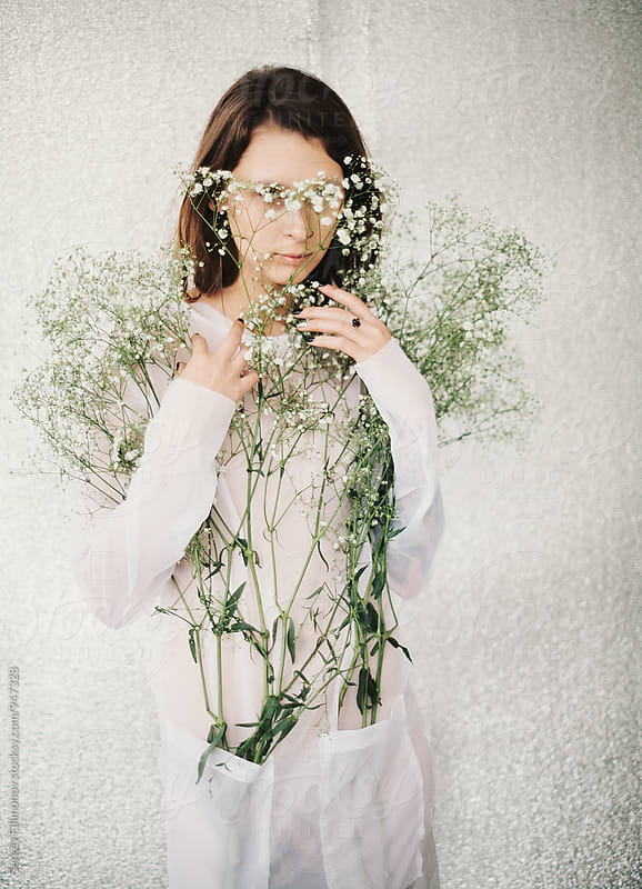 woman hide behind small white flowers by Sergey Filimonov for Stocksy United