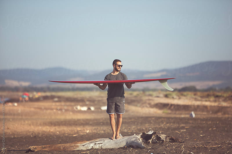 A surfer with his brandnew surfboard on the beach by Silvia Cipriani for Stocksy United