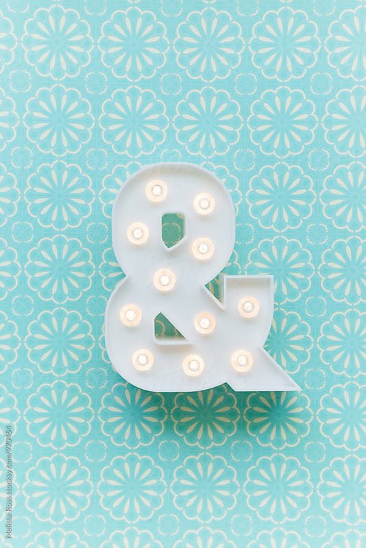 Ampersand marquee light on a blue background by Melissa Ross for Stocksy United