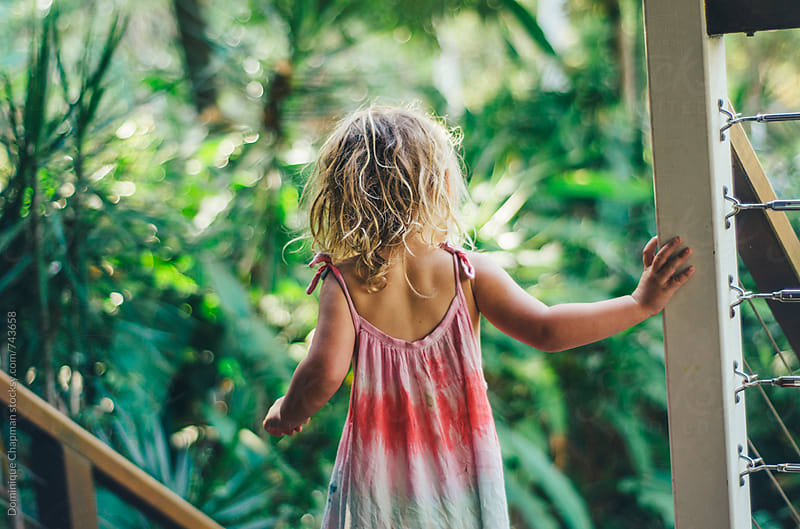 Little girl standing by tropical deck by Dominique Chapman for Stocksy United