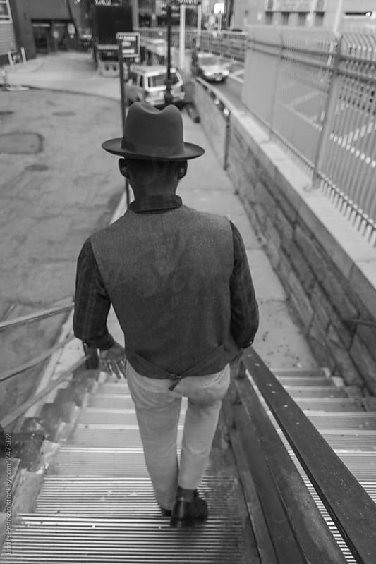 Young stylish man walking down stairs by Eddie Pearson for Stocksy United