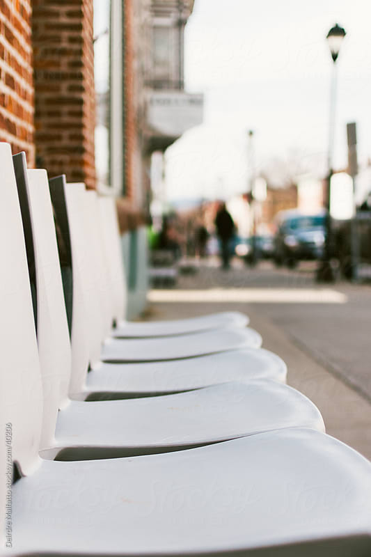White chairs in a row on a city sidewalk by Deirdre Malfatto for Stocksy United